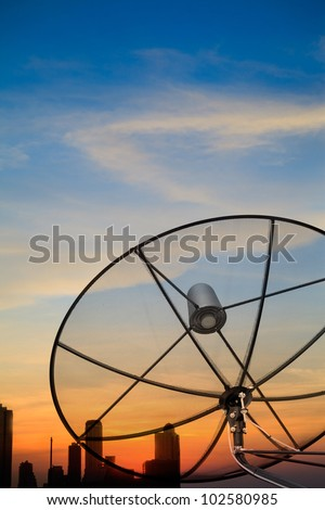 Black antenna satellite dish over twilight sky after sunset in cityscape - stock photo