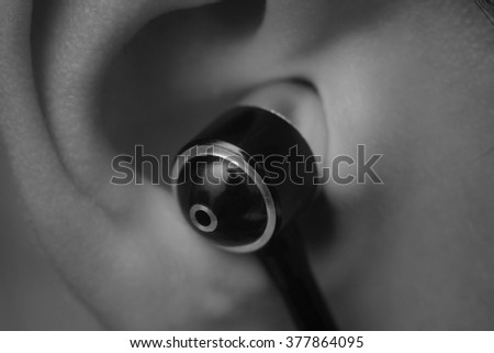 Black ?arphone (piston) in a woman's ear. Macro with soft focus. Blur. B&W.