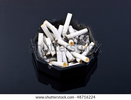 black ashtray with cigarettes on black table - stock photo