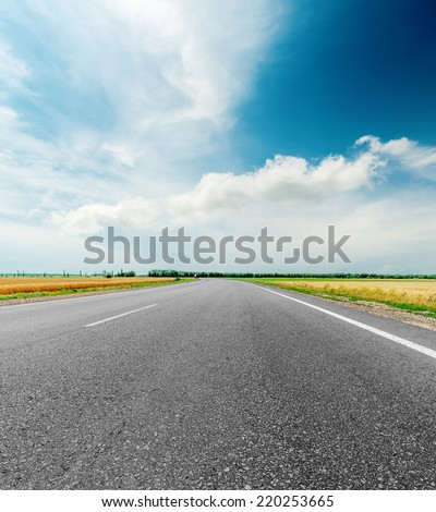 black asphalt road and clouds in dramatic sky - stock photo