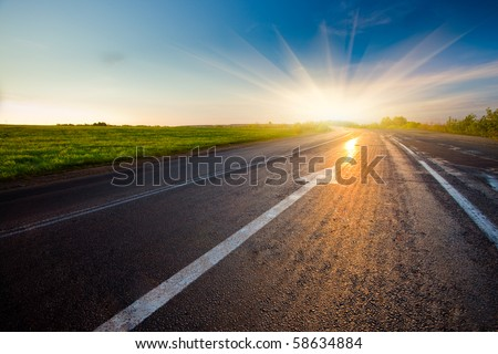 black asphalt road with arrow to sunset - stock photo