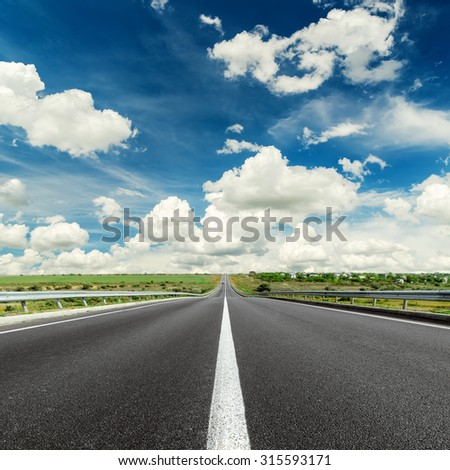 black asphalt road with white line on center and dramatic sky over it - stock photo