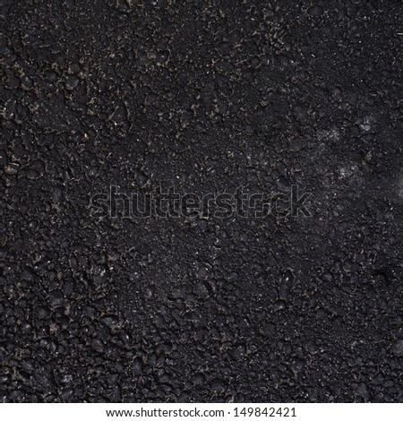Black asphalt surface fragment as a background texture - stock photo