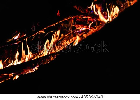Black background with flames and burning coals of the log.