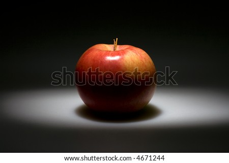 Black background with highlighted red apple in the center.