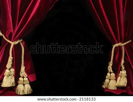 black background with red velvet drapes and gold tassel
