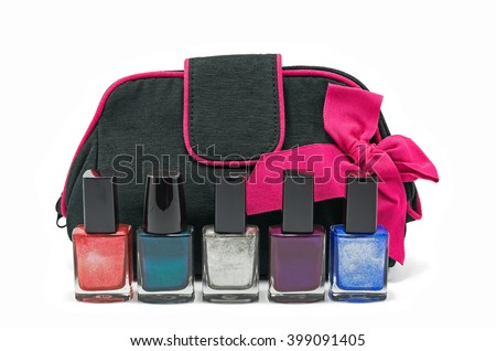 Black bag for cosmetics and accessories with a pink bow and bottles of multicolored nail polish isolated on a white background - stock photo
