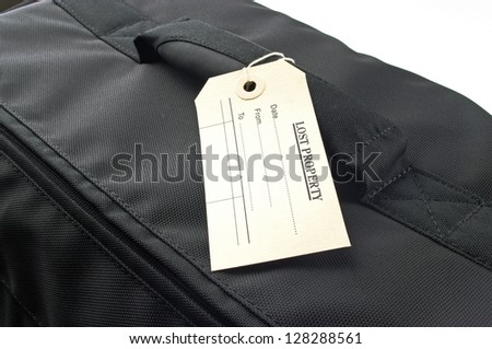black bag with a lost property label on the handle - stock photo