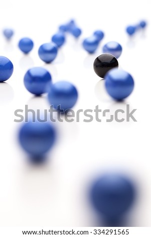 Black ball is hiding behind blue balls - stock photo