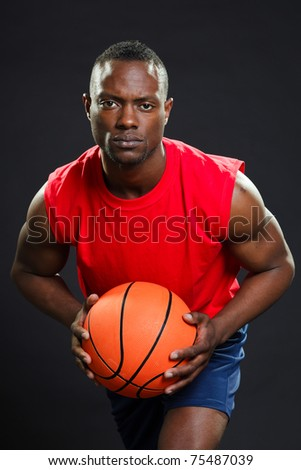 Black basketball player with red shirt and blue shorts holding basketball. - stock photo