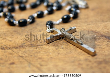 Black beaded rosary on rustic wood background - stock photo