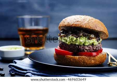 black bean burger with mashed avocado, caramelized onions and tomatoes. toning. selective focus