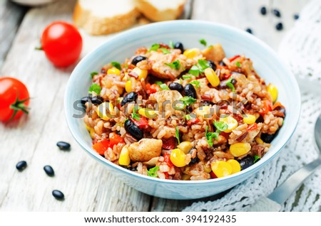 Black beans, corn and tomato red and white rice with chicken. toning. selective focus - stock photo