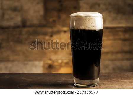 Black beer on wooden background - stock photo
