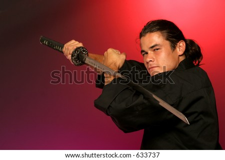 black belt holds katana a single edged  Japanese sword in warm red light - stock photo