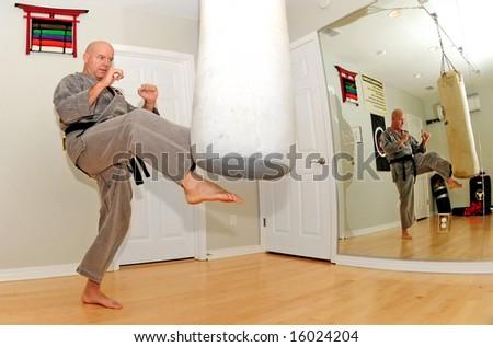 Black belt karate expert working out in dojo - stock photo