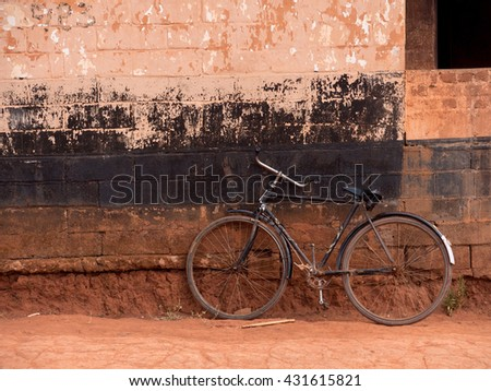 black bicycle leaning against the wall  - stock photo