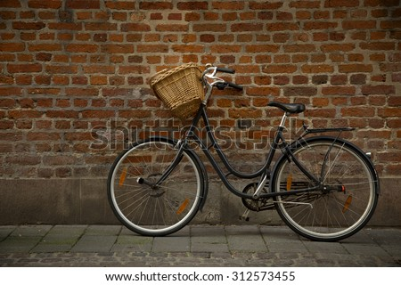 Black bicycle with straw basket along a brick wall - stock photo