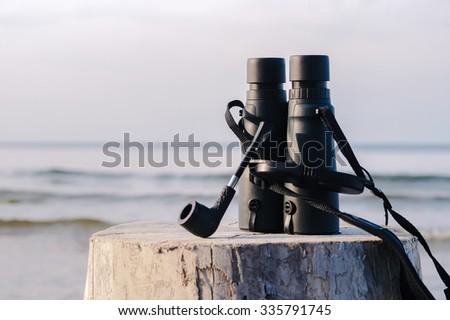 Black binocular and tobacco pipe - stock photo
