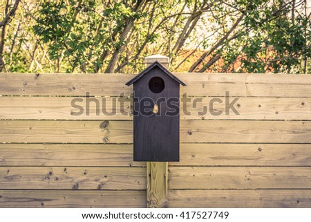 Black bird house on a fence in the summer - stock photo