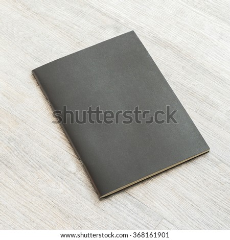 Black blank leather cover book template on white grey color wooden table background: Empty business notebook cover on light gray colour wood floor: Closed school student binder note pad on desk  - stock photo