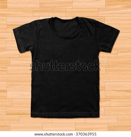 Black blank t-shirt on wooden background - stock photo