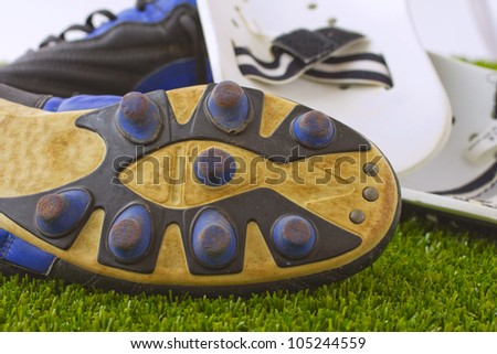Black, blue and white football shoes over green grass - stock photo