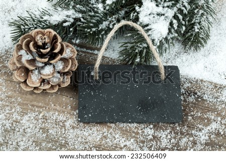 Black board of slate on old rustic wooden background, with snow - stock photo