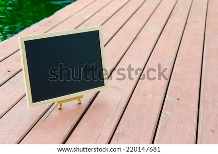 Black board on wood floor for copy space - stock photo