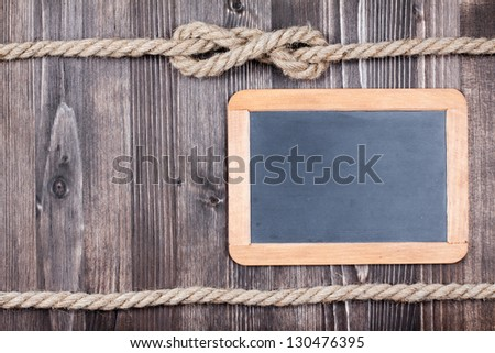 Black board on wooden planks with rope background - stock photo