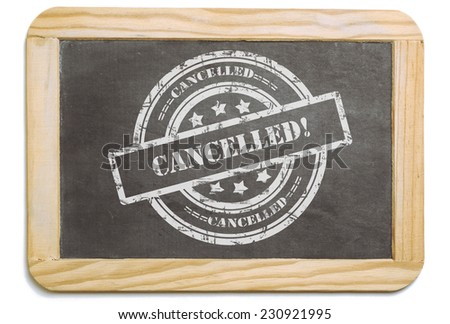 Black board with wooden frame, layered grunge design chalk message in stamp form: Cancelled. Isolated on white background. - stock photo