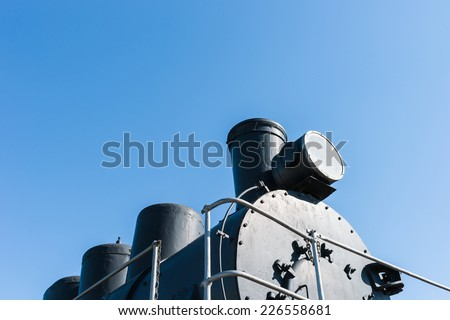 Black boiler of a steam locomotive against the background of clear blue sky. You can see an electrical headlight, chimney or smokestack, steam and sand domes - stock photo