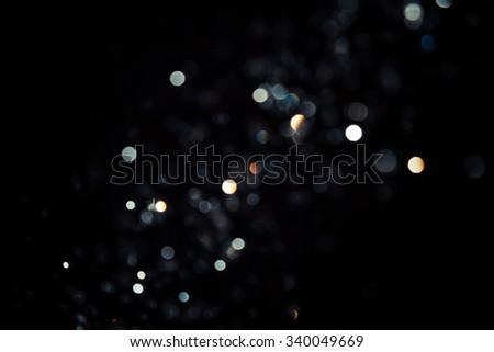 Black bokeh texture on black background - stock photo