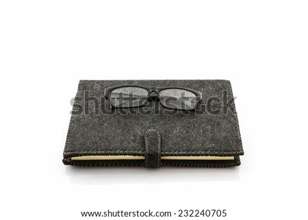 Black book with glasses on white background.  - stock photo