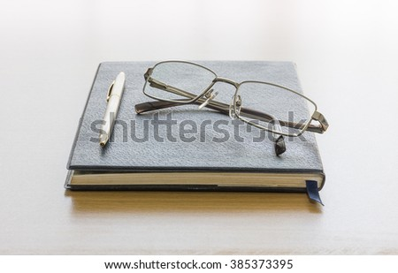 Black book with glasses on wood background - stock photo