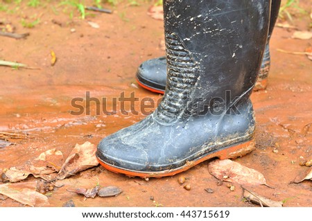 Black boots in muddy ground - stock photo