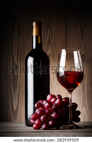 Black bottle and glass of red wine with grapes on wooden background