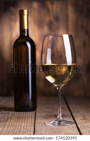 Black bottle of wine and wineglass on the wooden background   - stock photo