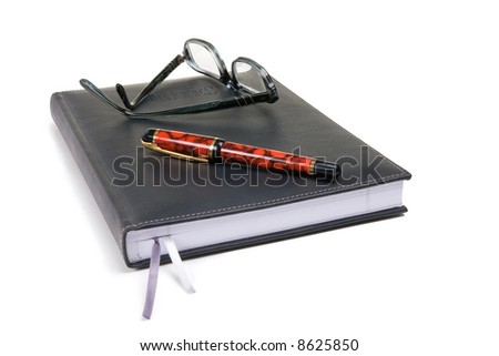 Black bound note pad with reading glasses and fountain pen - stock photo