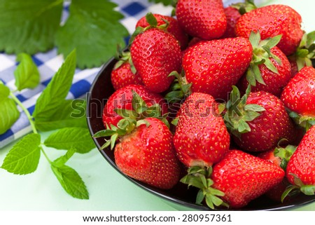 Black bowl filled with juicy fresh ripe red strawberries  - stock photo