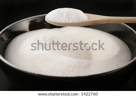 black bowl of plain white sugar with a wooden spoonful over it - stock photo