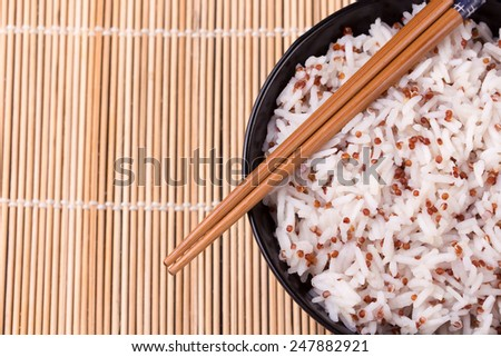 Black bowl of white steamed rice mixed with quinoa and chopsticks on bamboo mat. Copy space. - stock photo
