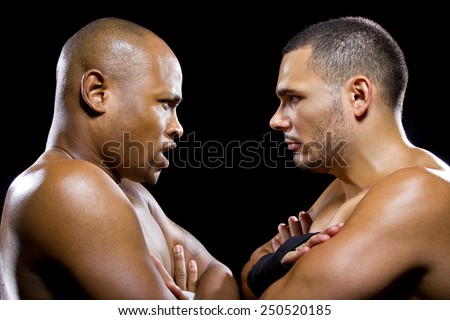 black boxer posing with latino opponent on a black background - stock photo