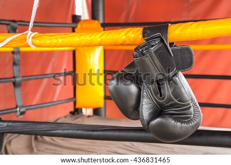 Black boxing gloves hang on hanging on ropes of ring. - stock photo