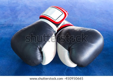 Black boxing gloves with two rolls of hand bandage on blue exercise mat. - stock photo
