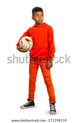 Black boy dreams of becoming a famous football player. Boy with football ball. - stock photo