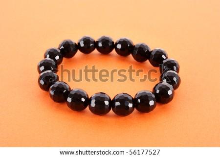 Black bracelet on yellow background - stock photo