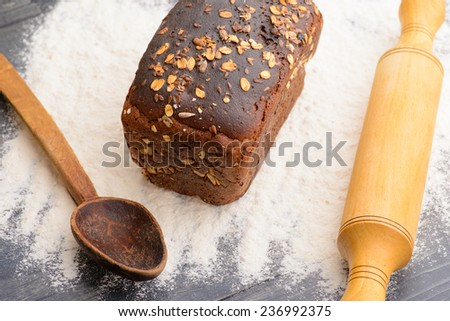 black bread flour with a spoon and a rolling pin on the table - stock photo