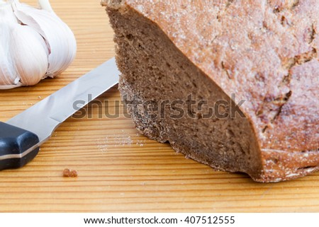 Black bread, knife and garlic on the wooden table