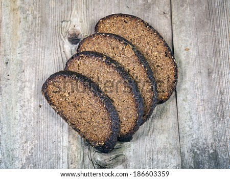 Black bread on a wooden background - stock photo